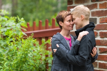 Two girls hugging front of fence and they look each other, horizon format