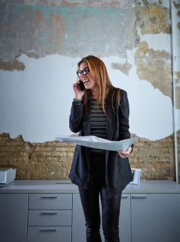 Architect woman talking phone holding plan paper at office