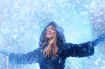 Young woman with falling snow winter portrait.