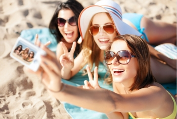 summer holidays, vacation and beach concept - girls taking self photo on the beach