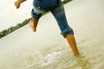 Low section view of a woman kicking water on the beach