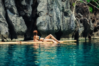 A beautiful young woman in a swimsuit is relaxing on a bamboo raft in a tropical lagoon