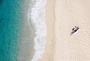 View of young couple resting on tropical beach, lots of copyspace