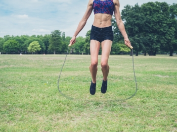 A fit and athletic young woman is skipping with a jump rope in the park on a summer day